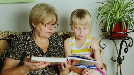 great story : Grandmother reading a book for girls