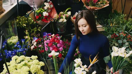 florista : Beautiful woman makes bouquet in flower shop