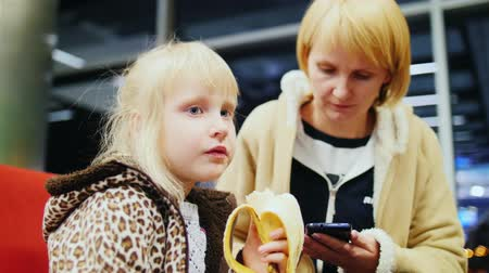 muz : little girl eating a banana at the airport with her mother who writes SMS