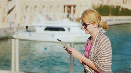 żaglówka : A female tourist enjoys the tablet on the background of yachts