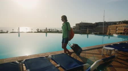 bagagem : Silhouette of a woman, which runs along the pool. driven travel bag. Steadicam hot
