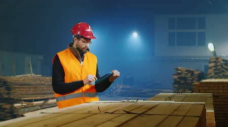 comprimido : Warehouse worker uses a tablet, according to the quantity of goods or construction materials