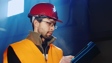 felügyelő : Worker in overalls and a helmet uses a tablet
