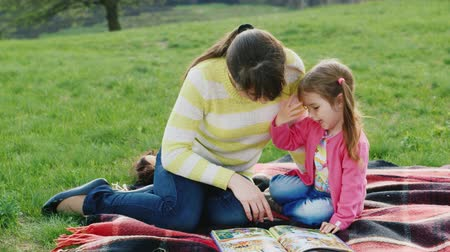nanny holding : Mum reads a fairy tale daughter in the park Stock Footage