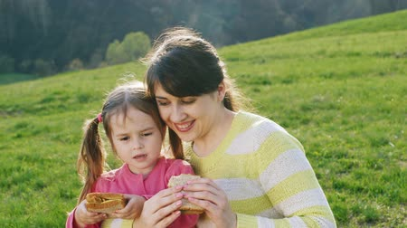 feed on : Mother and daughter eating sandwiches at a picnic