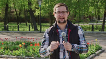 novinář : Male reporter with a microphone tells news camera. It should be in the spring park on a background of trees and flowers