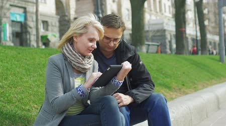 társkereső : A couple enjoys the tablet in the spring city, at the rear of the building plan and walking people