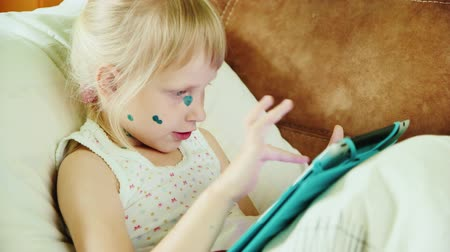 chickenpox : Girl suffers chickenpox, lying in bed and playing on the tablet