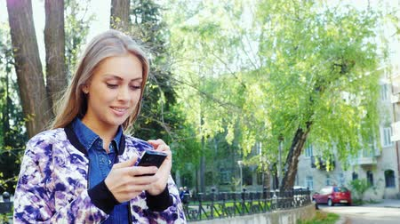 okos telefon : Attractive woman enjoying smart phone in a city park