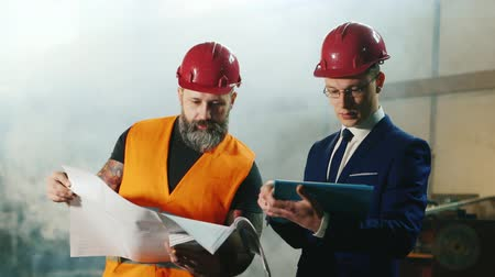 felügyelő : Intelligent engineering and brutal bearded construction worker studying drawings. Stock mozgókép