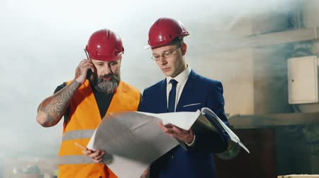 strojírenství : Teamwork of builders and engineering. Construction worker talking on the radio, an engineer studying blueprints