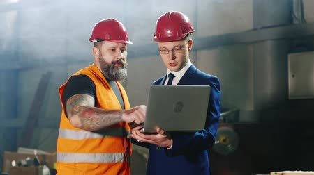 felügyelő : Engineer in helmet and bearded construction worker working with laptop in a warehouse or construction site Stock mozgókép