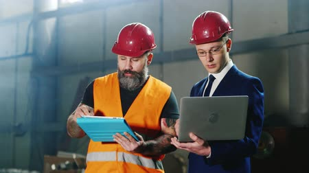 felügyelő : Advanced technology at the construction site - the architect and builder is working with the device - laptop and tablet