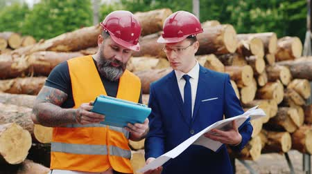 felügyelő : Business partners are discussing construction issues. Against the background of the stack of building woods