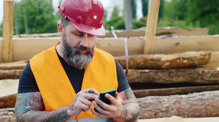 plumber : Brutal builder with a beard and tattoos sitting on the logs, using a mobile phone Stock Footage