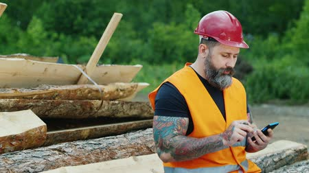 борода : middle-aged man with tattoos and beard enjoys a smartphone, sms writing. He is very serious or upset, sitting on a pile of logs construction