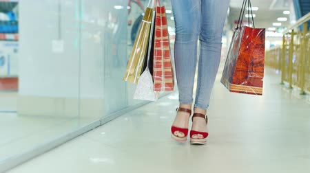 három ember : Womans legs in fashionable shoes on a high platform, go to the mall. It carries a lot of packages for shopping