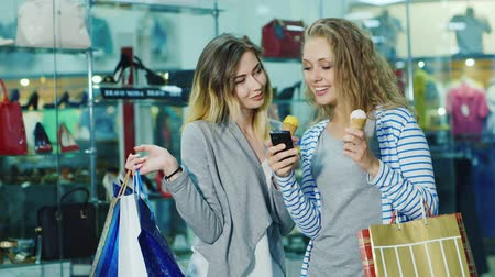 покупка товаров : Two young women with shopping bags eating ice-cream and consider something on the phone. Smile, it is against the background of windows in the store Стоковые видеозаписи