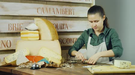 cheese packaging : Young woman seller packs a piece of cheese at the counter