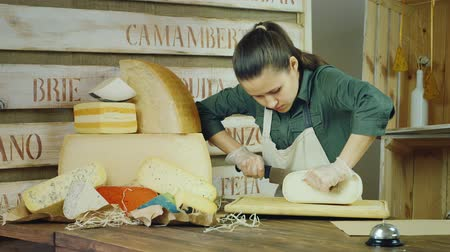 баланс : The seller cheese at work - cutting the cheese with a knife