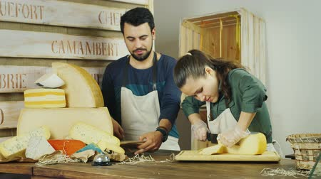 cheese packaging : Sellers man and woman working together in a cheese shop Stock Footage