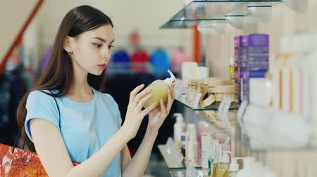dezenfektan : Attractive brunette chooses liquid soap in a perfume shop Stok Video