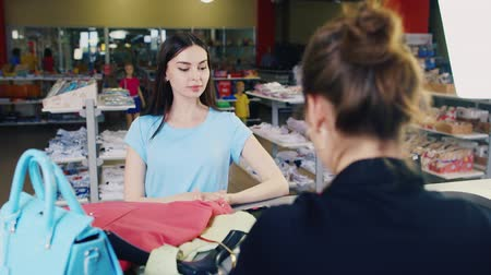 Attractive woman pays for goods - summer dresses and handbag. In a clothing store Stock mozgókép