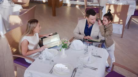 обедающий : Family ordering dinner in a cafe or restaurant.