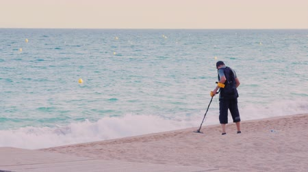 perdido : Lloret de Mar, Spain - June 15, 2016: Man with metal detector looking for coins and valuables on the beach