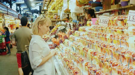 spanyolország : Barcelona, Spain - June 15, 2016: Woman tourist looking at a large storefront with sweets and flowers. The famous la Boqueria market