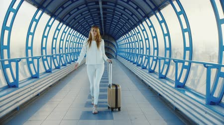 идущий : Young business woman with travel bag on wheels is on the transition from the terminal at the airport or train station