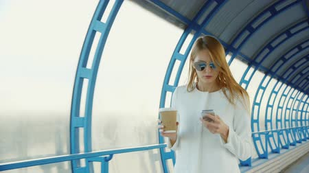 gidip : All business on the go. Business woman with a cup of coffee and the phone quickly goes on the tunnel of glass Stok Video