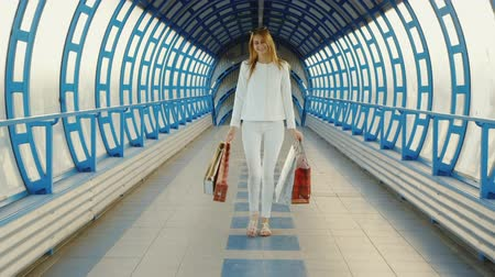 transportar : Steadicam shot: Stylish young woman with shopping bags talking on modern glass transition or a tunnel Stock Footage