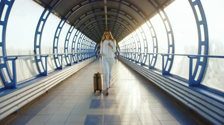 bagagem : Stylish business woman dressed in white comes with travel bag on the tunnel of glass or transition. Light of the setting sun, enjoys a telephone.