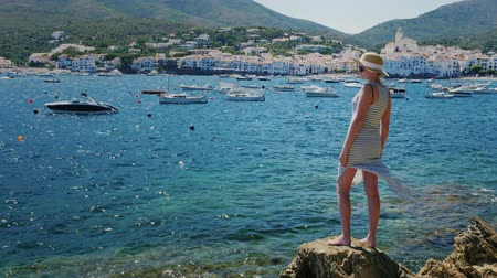 паром : Steadicam shot: A woman stands on the rocky shore and admiring the beautiful view of the sea and the resort town of Cadaques in Spain Стоковые видеозаписи