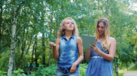 móvel : Two young woman walking in the park, laughing and holding the tablet in hands Vídeos