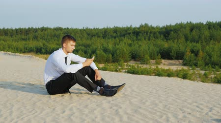 bağlantılı : Always connected. Young businessman with phone sitting on sand on a background of picturesque forest