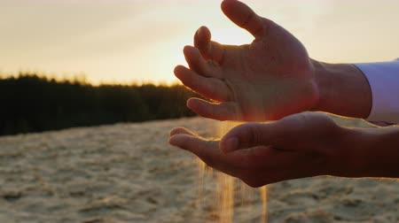 philosopher : Hands of businessman man in a white shirt sifted sand through his fingers at sunset. The concept - a period of time, change Stock Footage