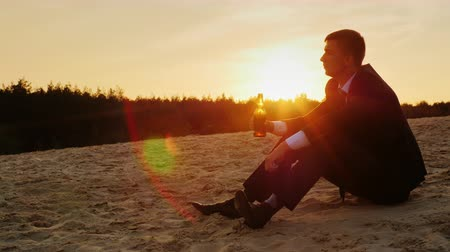 depressão : Young businessman in a suit sitting in the sand and drinking beer from a bottle. The collapse, depression and bankruptcy