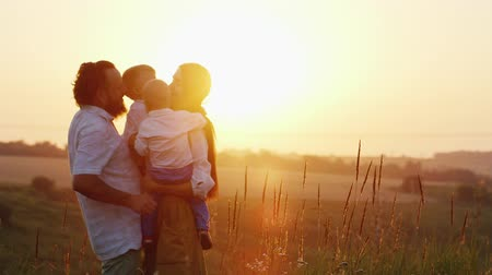 family life : Big family hugging at sunset. Parents and two children