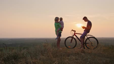 otec : The family welcomes the sunset. Son sits on the bike and is on the phone, mother and daughter looking at the setting sun