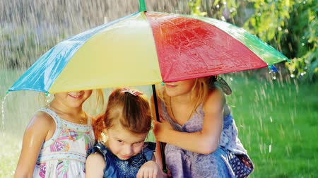 três : Three cheerful carefree girl under the umbrella of the rainbow colors. There is a warm rain. Happy childhood