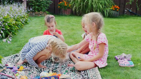 toy : Carefree children play with the cat in the yard.