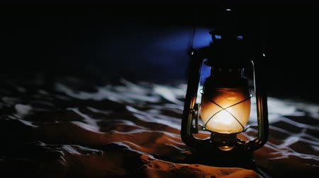 lampa naftowa : Old kerosene lamp shines. It stands on the sand at the beach in the dark. Beautiful blue smoke comes from the top Wideo