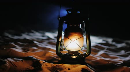 lampa naftowa : Vintage oil lamp standing on the sand, shines in the dark Wideo