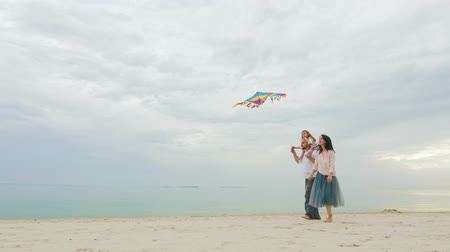 醫療保健 : Friendly young family playing with daughter, fly a kite. Against the backdrop of a beautiful sea and sky 影像素材