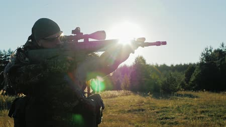 sniper scope : Soldier in camouflage with a gun goes forward, looking through the scope. Siluluet, the suns rays shine through the arms