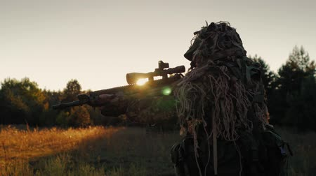 sniper scope : Steadicam shot: Sniper in a camouflage outfit moved cautiously, looks through the scope of weapons. At sunset