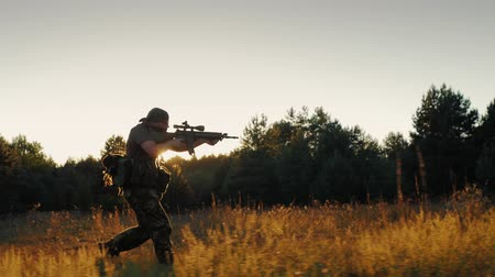 bulletproof : Steadicam slowmotion shot: An armed man running in the attack. Holding in hands the weapon, in the setting sun Stock Footage