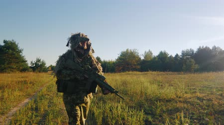 стрельба : Steadicam shot: Armed man in a camouflage suit and weapons goes on a country road
